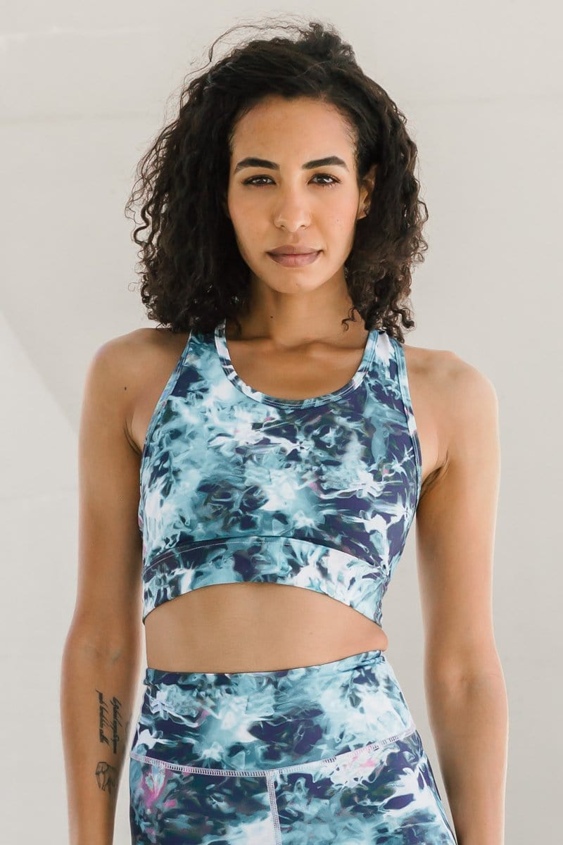 Woman with dark hair wearing ethically-made in Canada blue tie-dye longline sports bra.