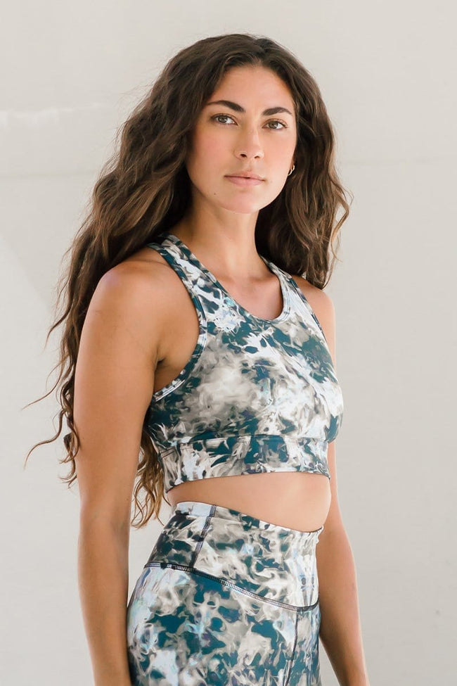 Woman standing in longline racerback sports bra featuring tie-dye print in brown, taupe, black and white. Ethically-made racerback sports bra designed and made in Canada available online shown by woman with long dark hair.