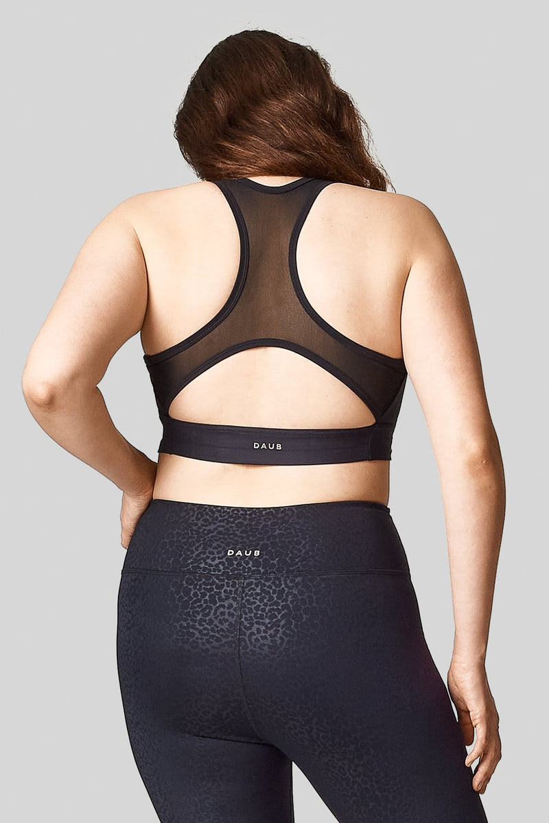 Back view of a woman wearing a plain black sports bra with mesh racerback. Paired with cheetah print leggings.