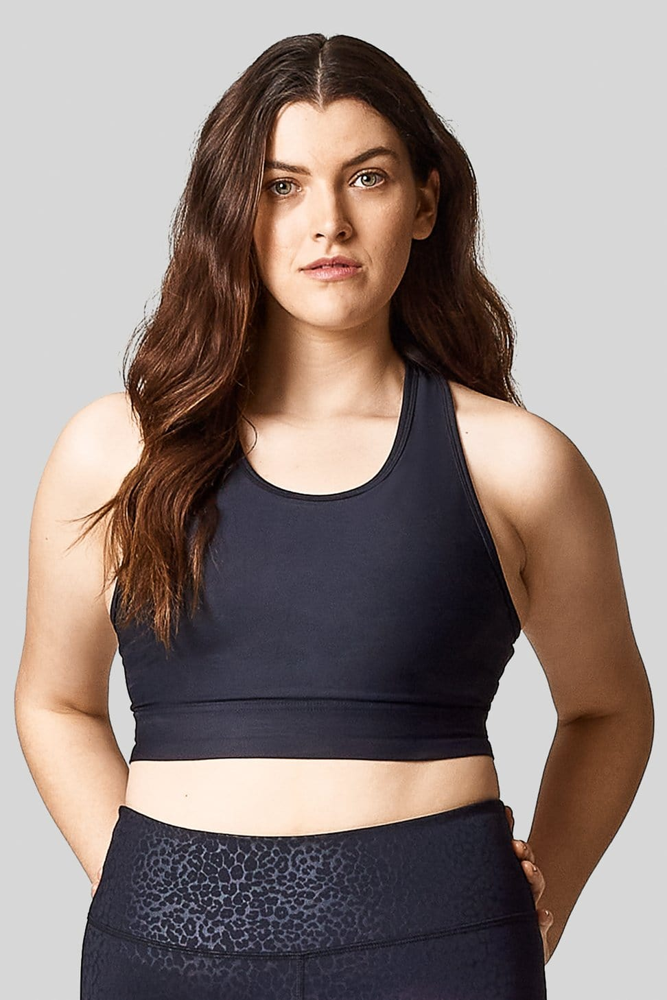 A woman wears a black long line sports bra with cheetah printed leggings.