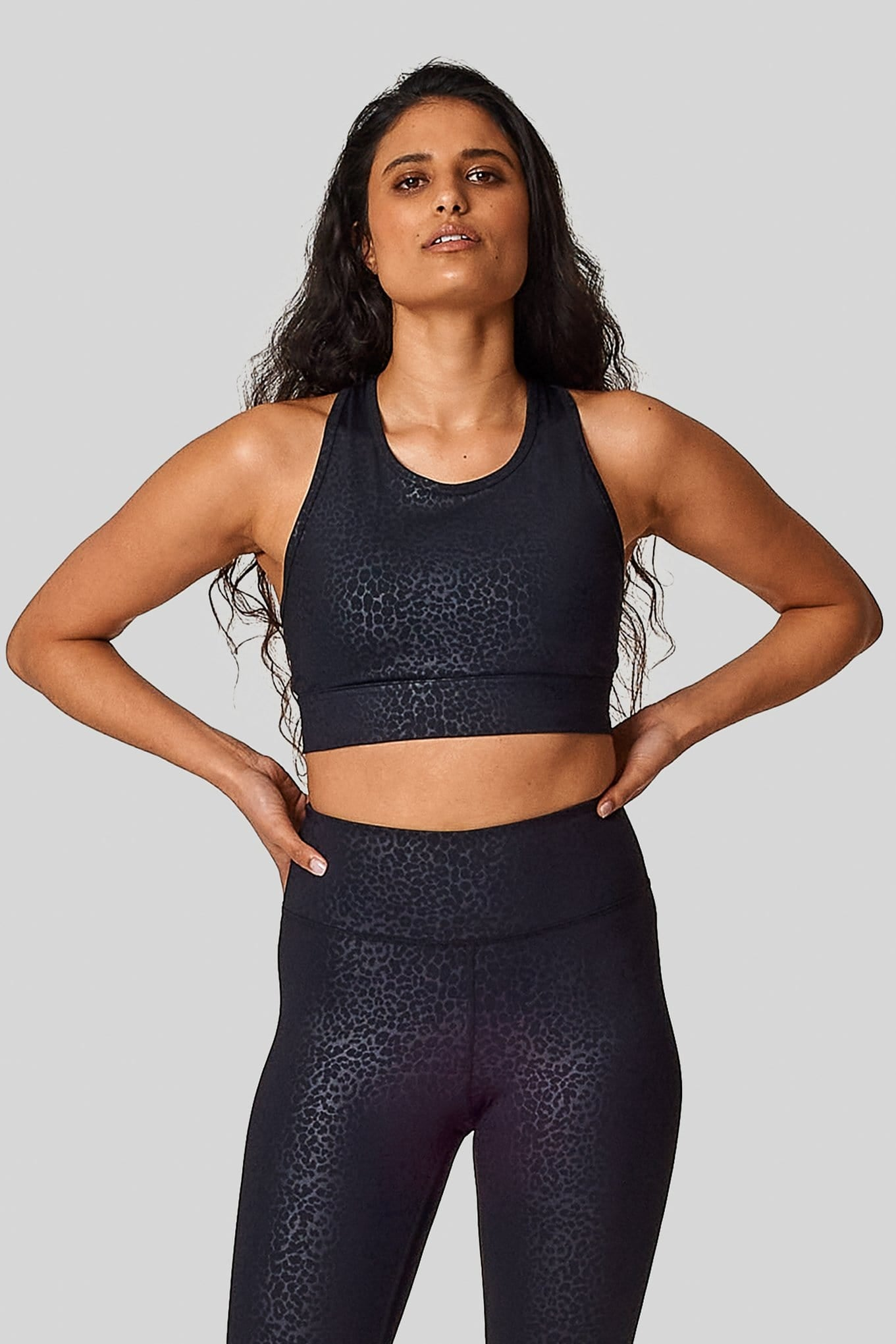 A matching cheetah sports bras & leggings set on a woman with her hands on her hips.