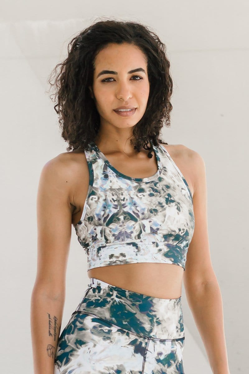 Woman with dark curly hair wearing ethically-made sports bra in white, black, brown and taupe.  Ethically-made activewear longline sports bra sets that are made in Canada available online.