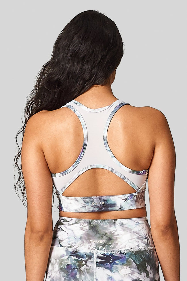 The back view of a woman wearing a sports bra with white mesh and a back cut out racerback sports bra.