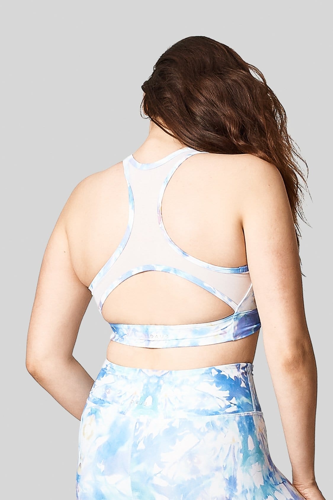 Back view of the mesh back racerback with cut out in light blue tie-dye with matching high waisted legging.
