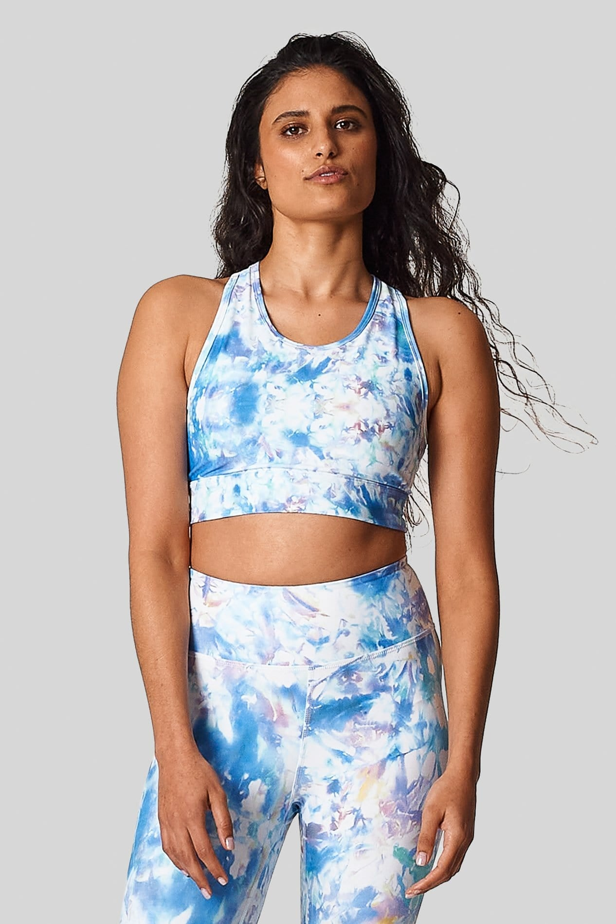 Light blue tie dye activewear set on a girl with brown hair.