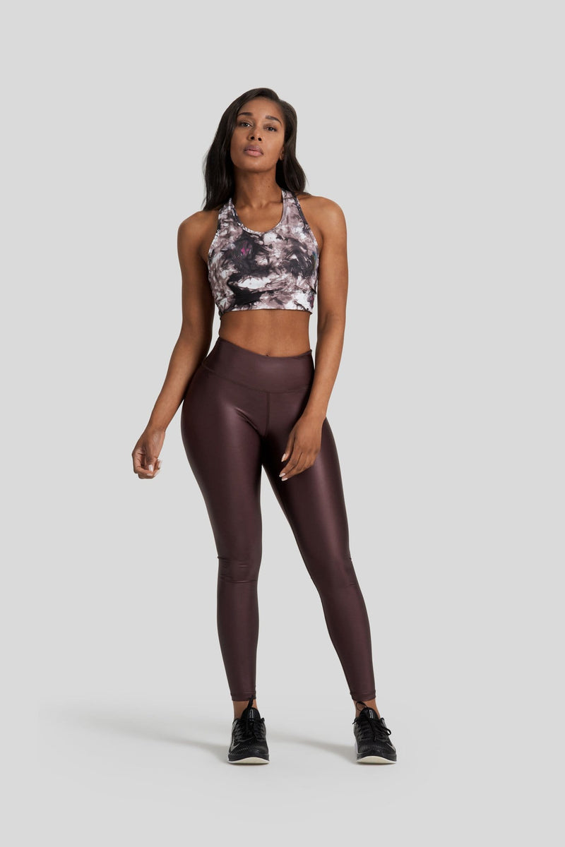 A woman is shown wearing hi gloss brown leggings and a tie dye brown sports bra