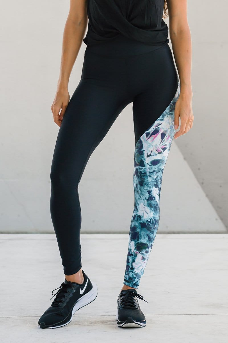 Woman standing wearing ethical, made-in-Canada black leggings with tie-dye accent leg featuring blue, white and green tie-dye.