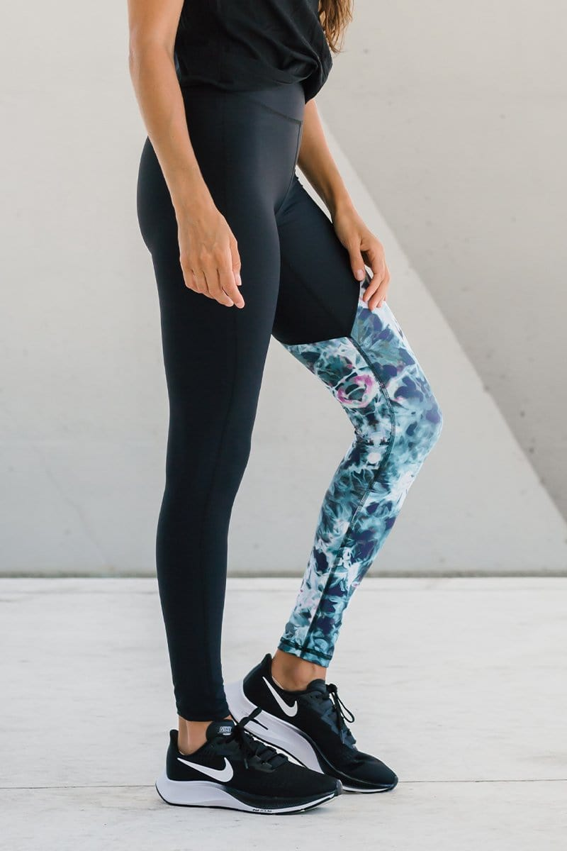 Woman wearing black top and blue, white and green tie-dye leggings. Ethical, made-in-Canada high-waisted leggings in hand-dyed tie-dye prints.
