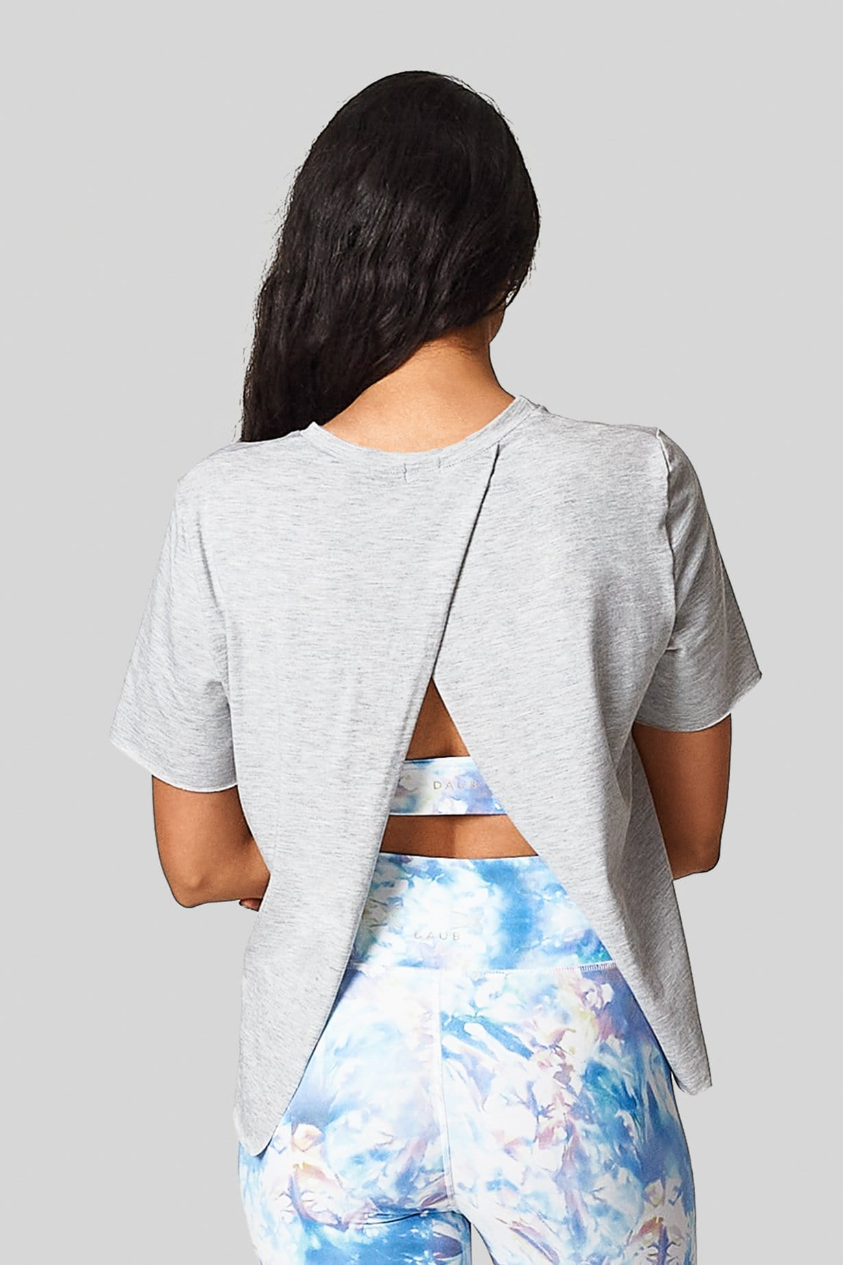 A woman wears a light heather grey t-shirt with an diagonal open back and tie-dyed sports bra and leggings.