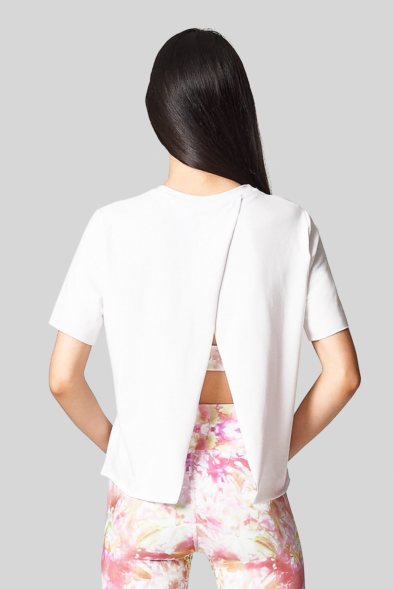 The back view of a woman wearing a white open back short sleeve tee-shirt with neon tie-dye leggings.