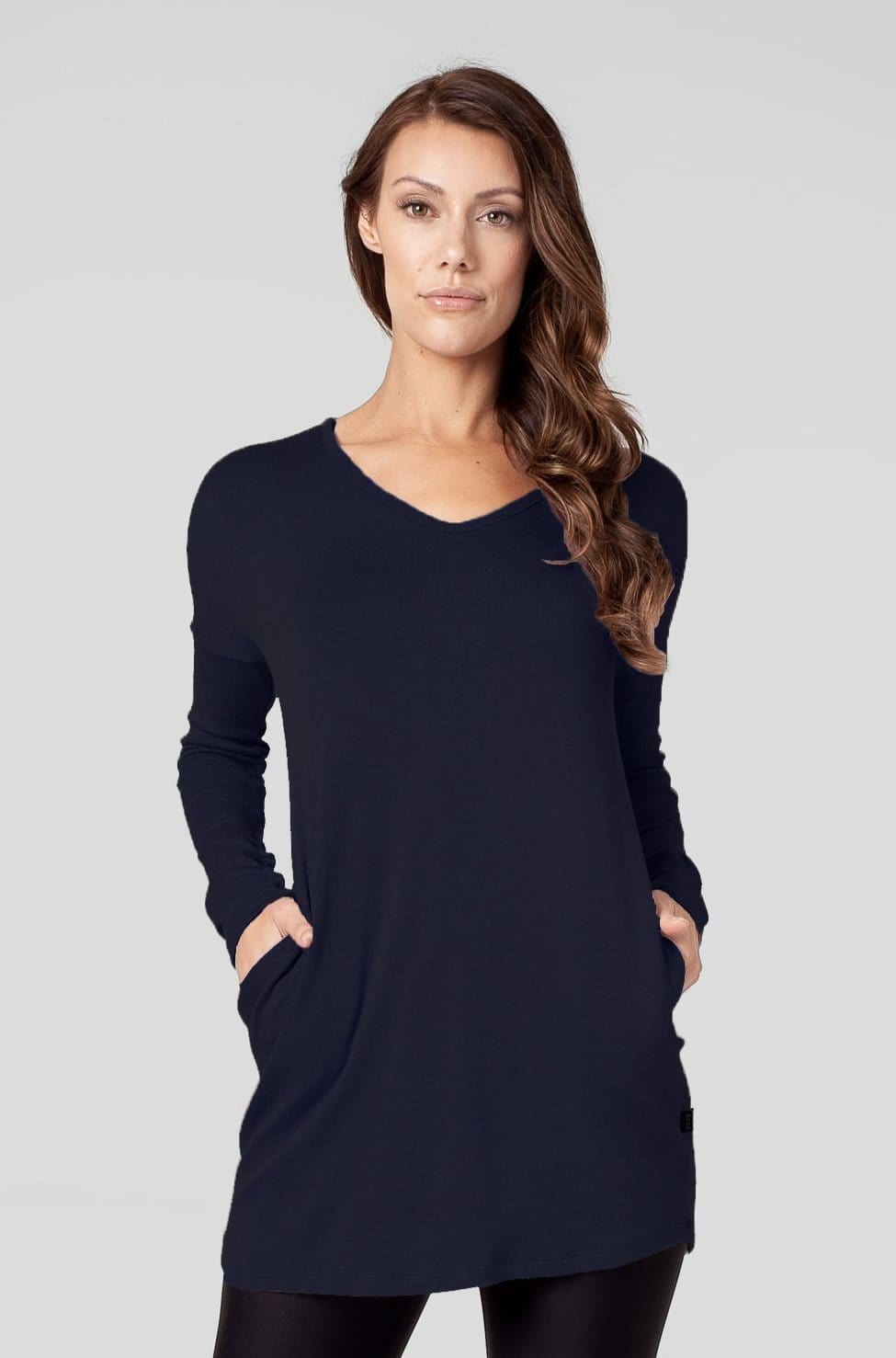 A woman wears a long sleeves navy tunic with her hands in the pockets.
