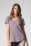 A brunette wears a light grey t-shirt made for barre, yoga and every day conscious consumers.