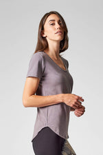 A brunette shows the side view of a short sleeve t-shirt in light soft grey.