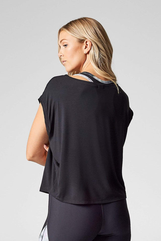 A blond woman is shown from the back wearing a black box shaped t-shirt, cropped at the hip.