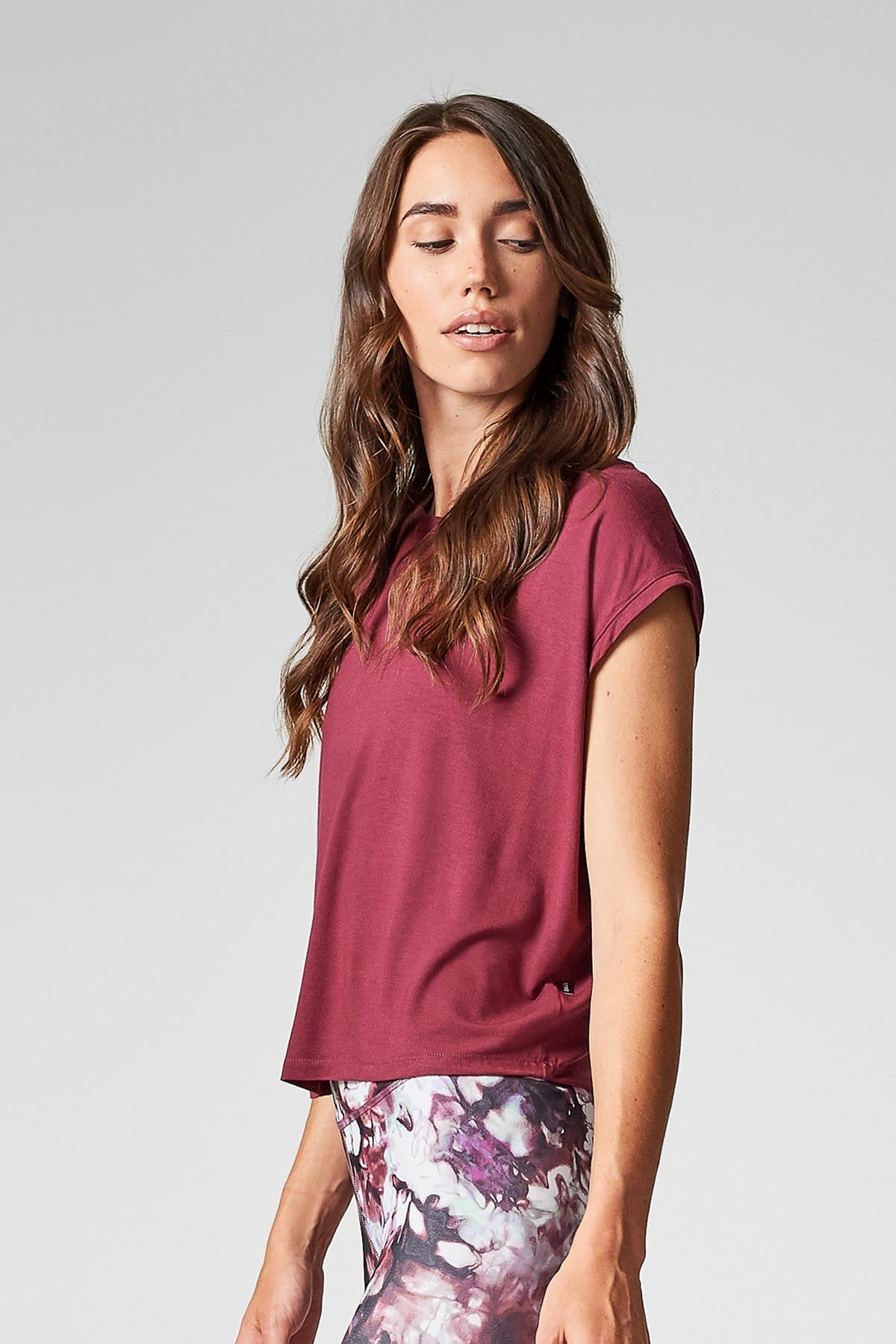 A brunette woman wears a burgundy colored box tee shirt and tie-dyed leggings