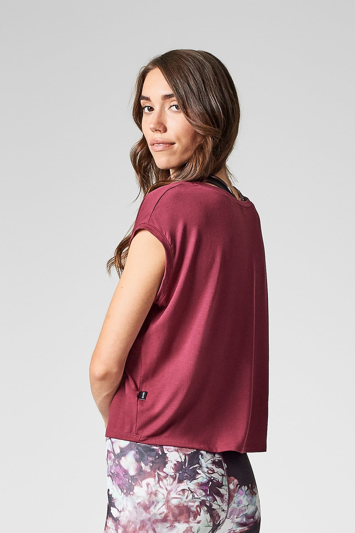 A brunette with long hair wears a burgundy t-shirt that is cropped & loose at the waist