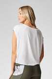 A blond woman wears a white boat neck, box tee shirt made from modal.
