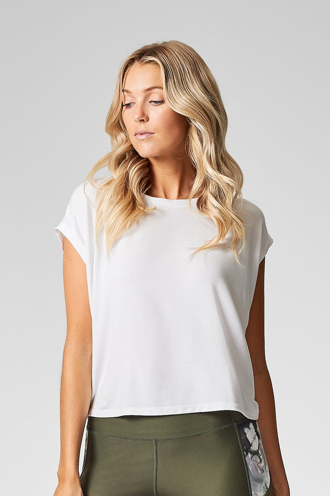 A woman with blond hair wears a white t-shirt made from modal that is cropped at the hip.