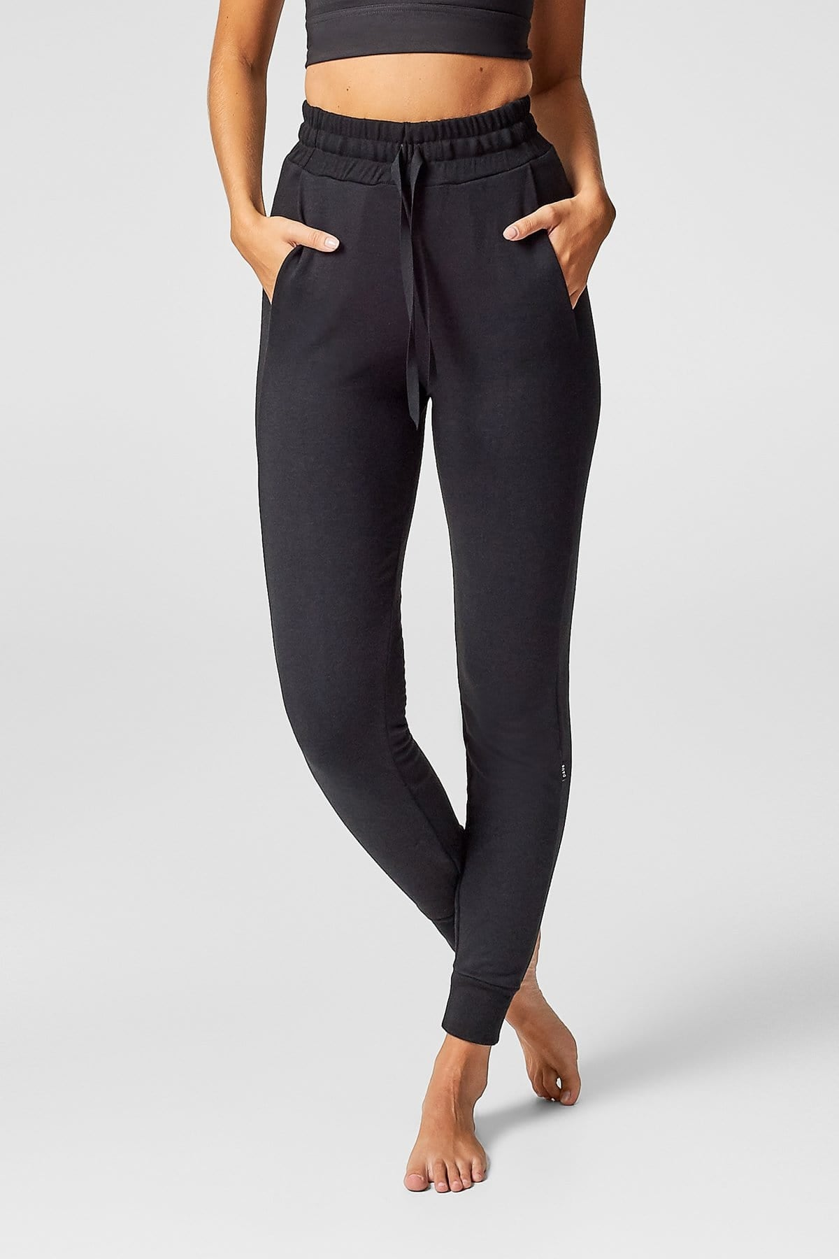 A tanned woman wears a pair of black fleece sweatpants with a drawstring.
