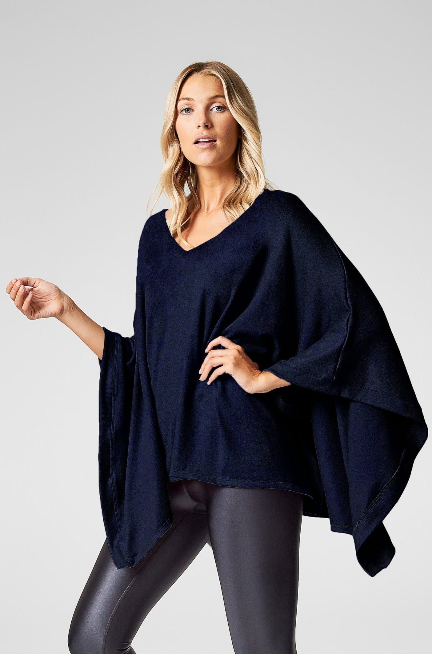 A woman wears a navy poncho with black liquid leggings.