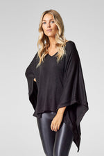 A woman stands with one hand on her hip, modelling a black poncho.