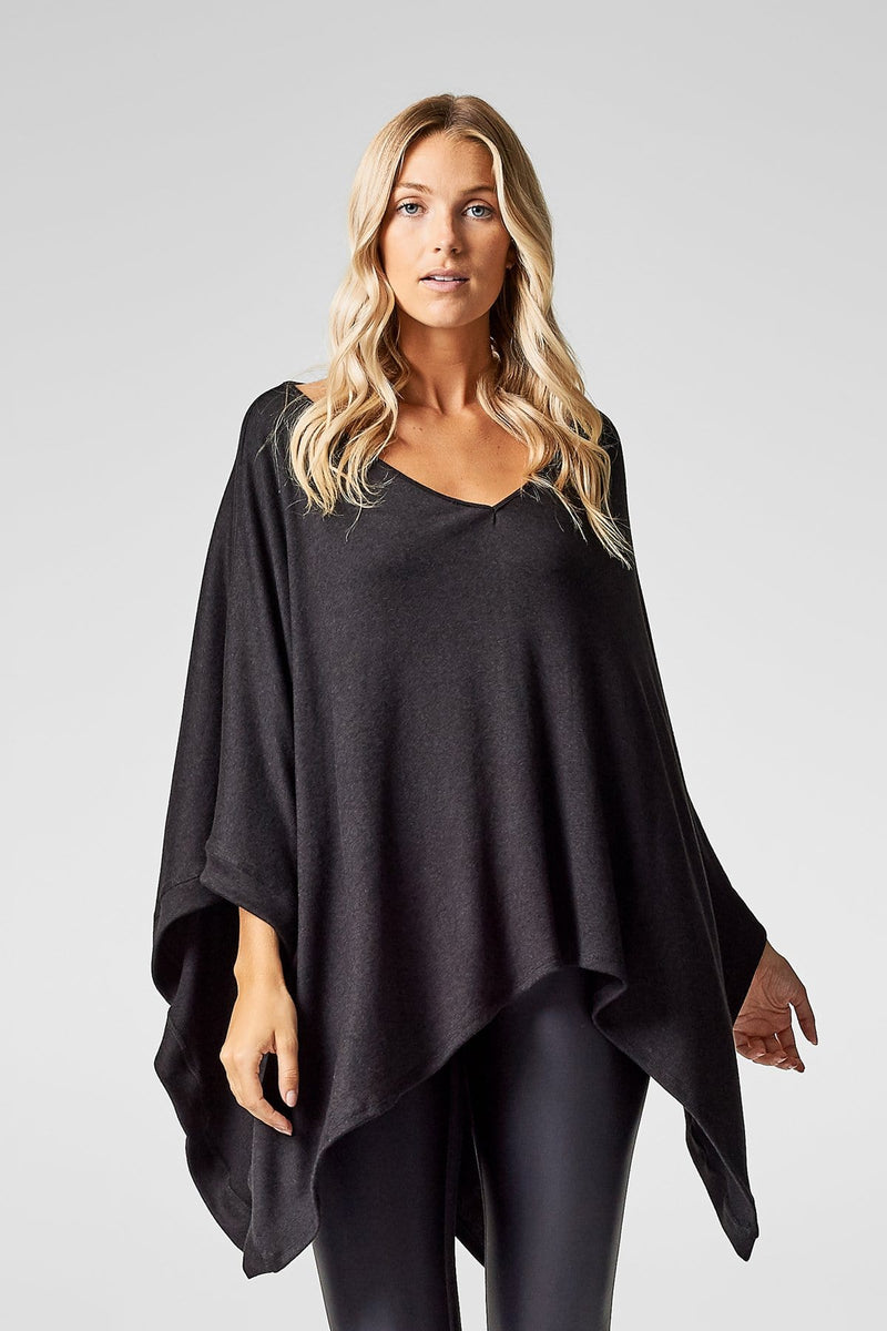 A woman wears a black poncho with black liquid leggings.