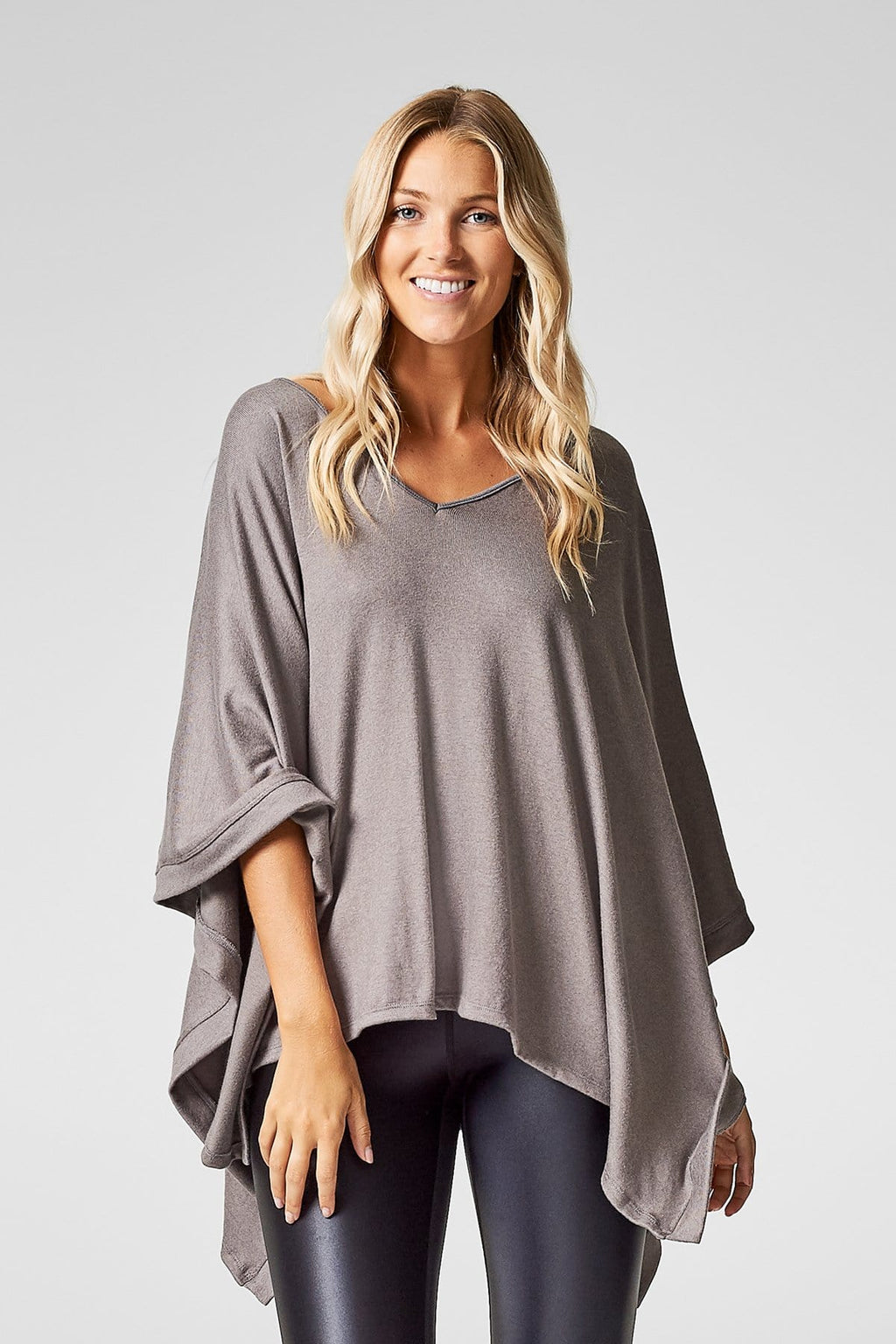 A woman wears a light grey poncho with black liquid leggings.