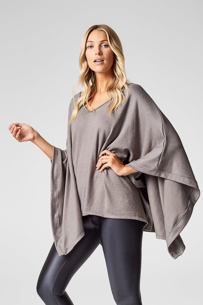 A blonde woman wears a light taupe poncho and stands with one hand on her hip.