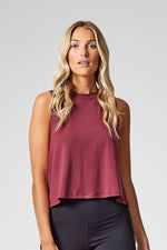 A woman models a short burgundy tank top.