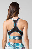 A woman's back is shown wearing a sports bra with a black mesh racerback and cutout detail.