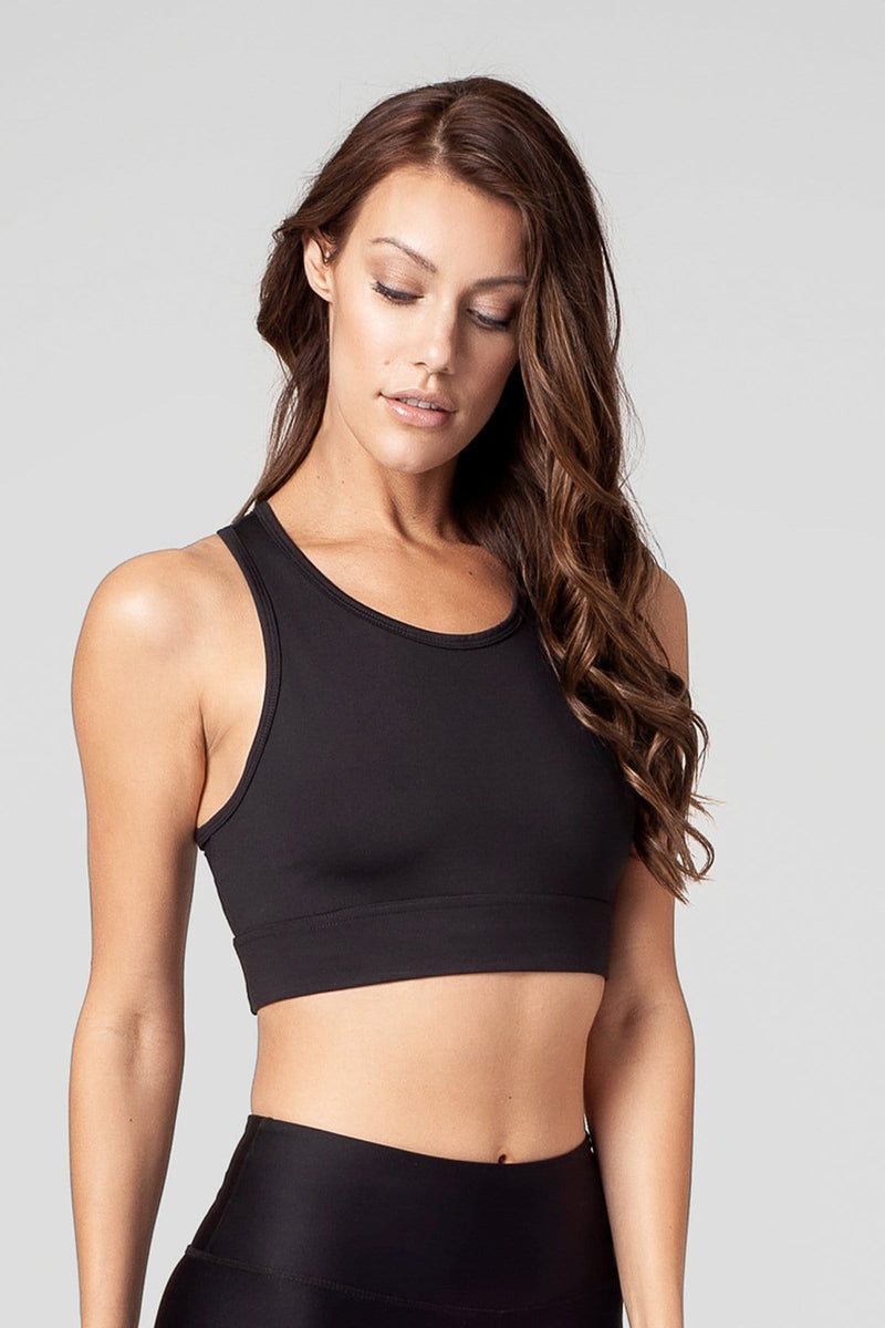 A brunette woman wears a black, long-line sports bra with good bust coverage.