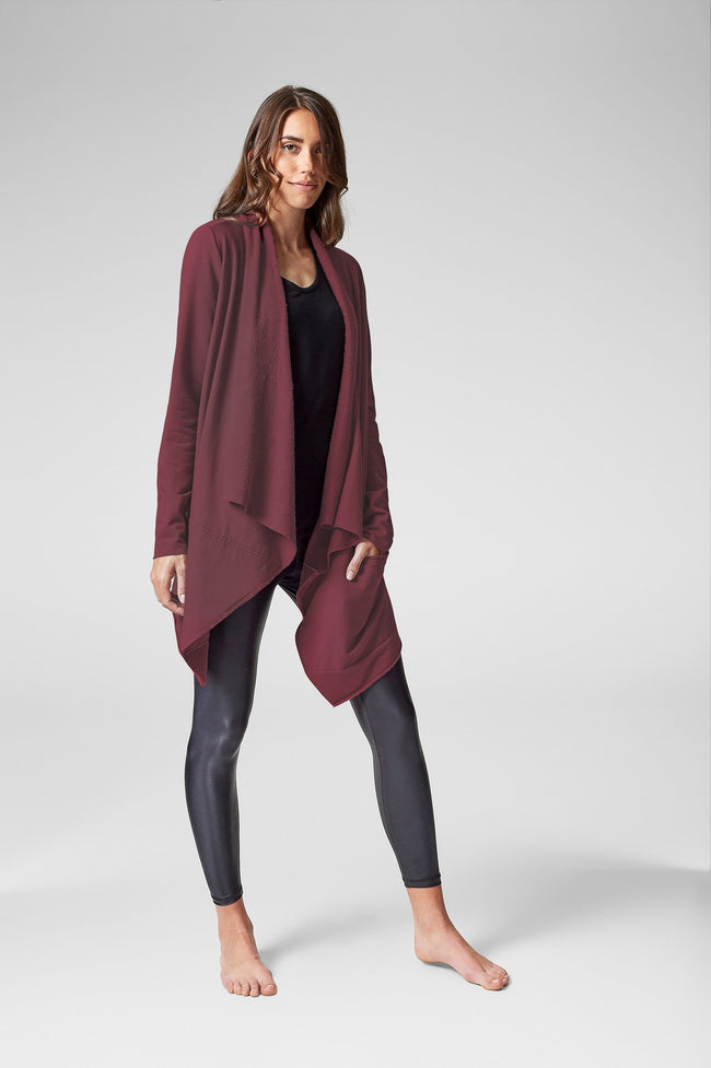A woman models a burgundy jacket worn with black leggings.