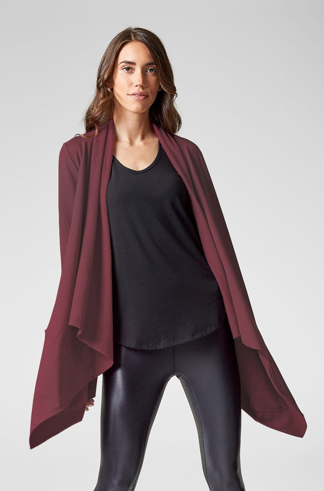 A woman is shown modelling a burgundy draped sweater jacket.