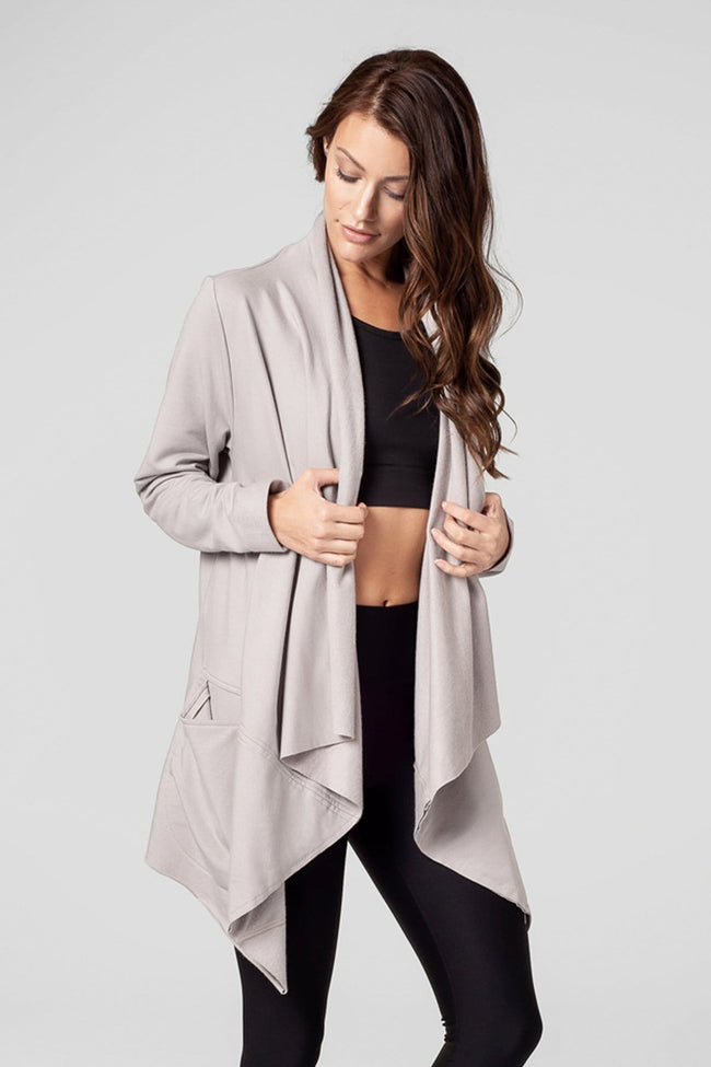 A woman models a taupe coloured sweater jacket.