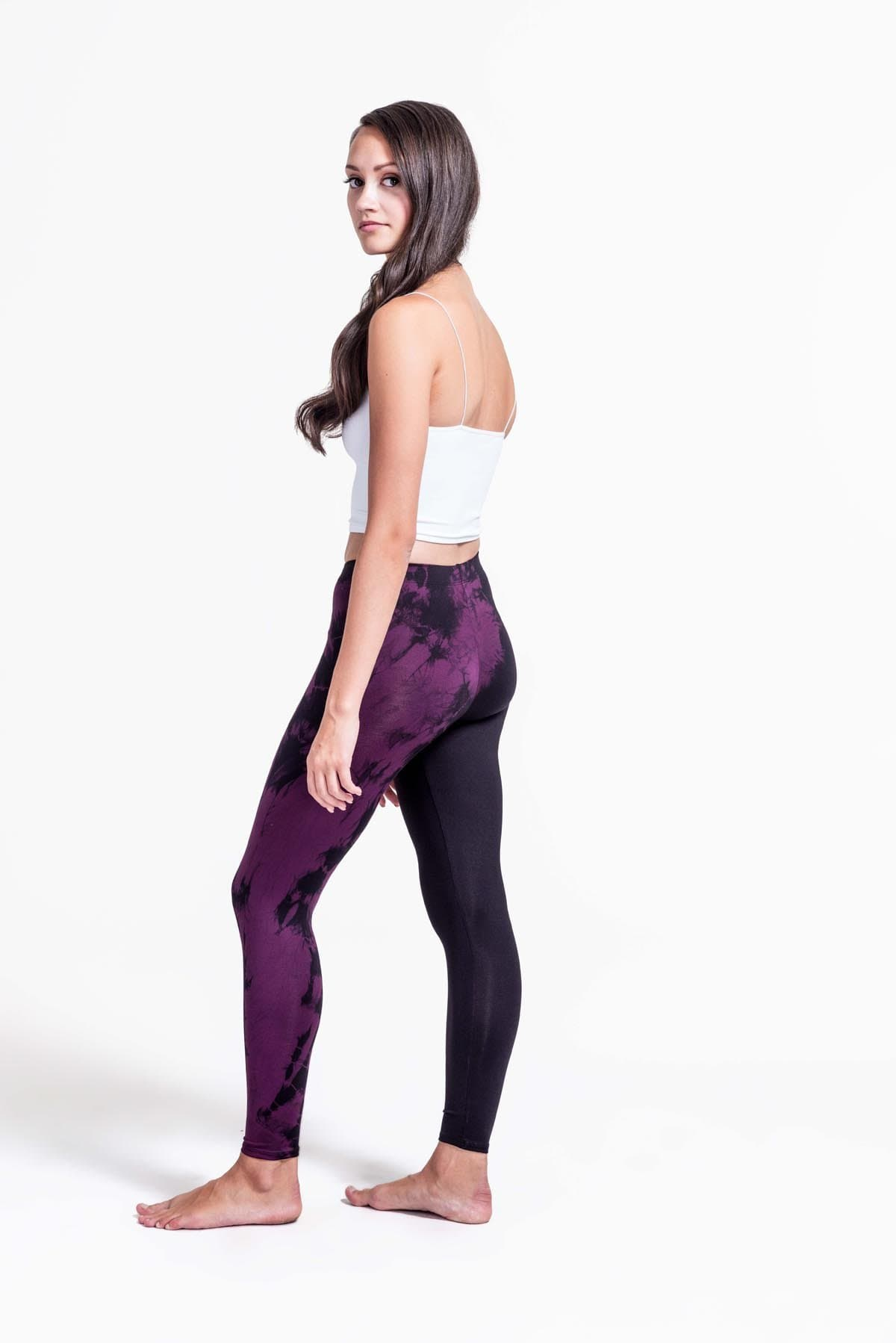 A woman with brown hair models a black sports bra and leggings. The right pant leg of the leggings is black, while the other is tie-dyed in plum and black.