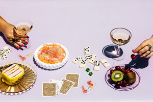 Table scene with cake on a plate, penis gummies in a bowl, champagne, and hands grabbing for fruit.
