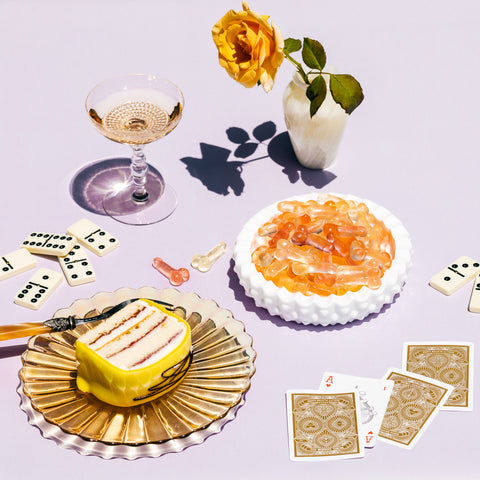 Table scene with bowl of gummies, glass of champagne, and cake on plate