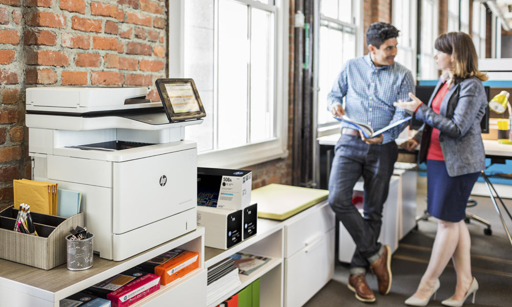 Urban office with exposed brick and HP desktop multifunction printer with LCD smart screen