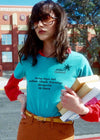 Girl at school with books wearing vintage blue 1970s women's graphic tee