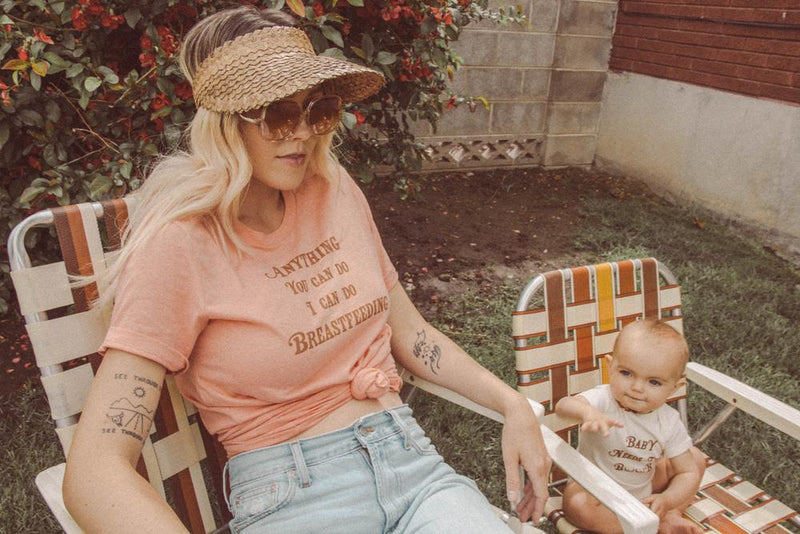 Mother and baby both sitting in lawn chairs wearing Top Knot Goods t-shirts