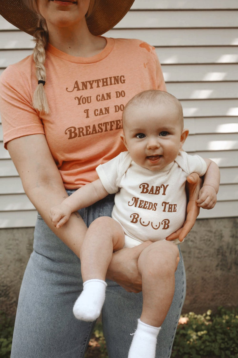 Mother holding baby that is wearing a funny baby onesie that says Baby Needs the Boob