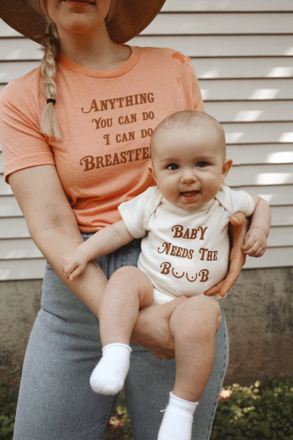 Mother holding baby that is wearing a funny baby onesie
