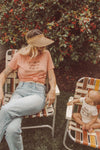 Mother and baby looking at each other while sitting in vintage lawn chairs