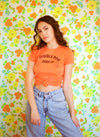 Brunette girl standing in front of a floral wall wearing jeans and orange ribbed t shirt that says Double Dog Dare Ya