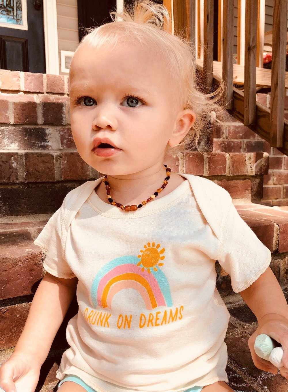 Baby girl wearing cute baby tee that says Drunk on Dreams with a colorful rainbow