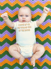 Baby with arms up laying on a striped blanket wearing the onesie that says I woke up on the wrong side of the boob