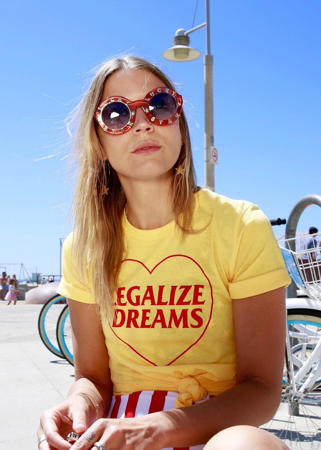Girl wearing yellow shirt with red writing that reads Legalize Dreams with a red heart outline
