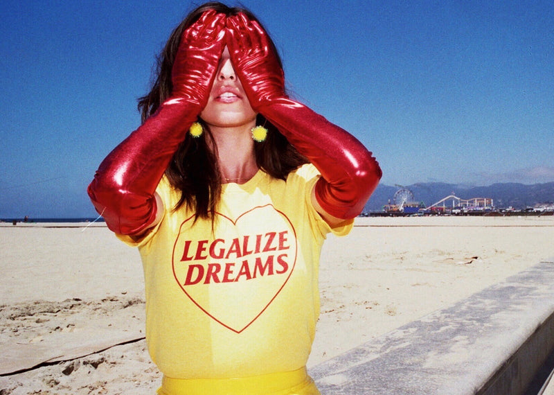 Girl wearing red gloves covering her eyes with her hands while wearing a yellow t shirt that reads Legalize Dreams