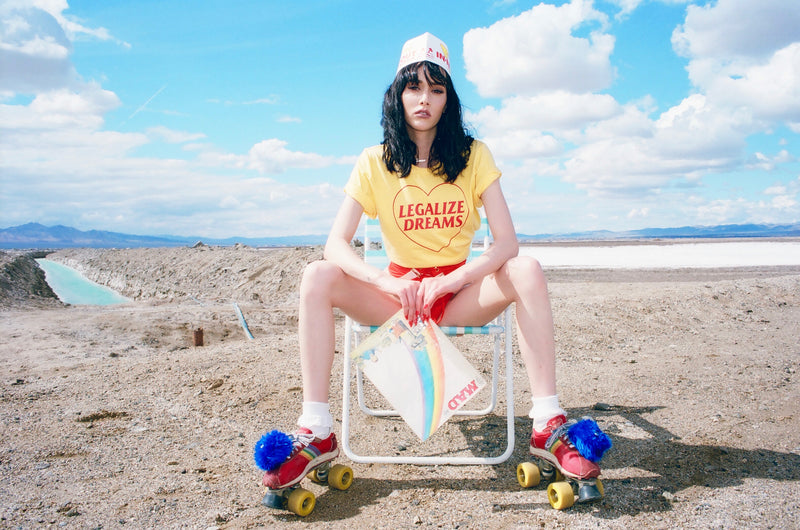 Girl sitting at the beach in lawn chair wearing roller skates and a yellow t shirt that says Legalize Dreams