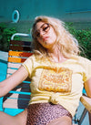 Girl in vintage lounge chair wearing a one piece bathing suit and yellow Top Knot Goods tee